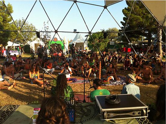 espectáculo musical, festival sostenible de música de verano. gente sentada en el suelo escuchando música. carpas blancas en el fondo, árboles a los lados