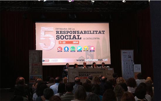 ponencia de la 5a semana de la responsabilidad social en Barcelona. 5 ponentes delante de una pantalla de proyección. público sentado escuchando. Catalunya