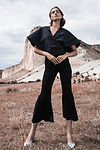 Women in black outfit standing in the desert