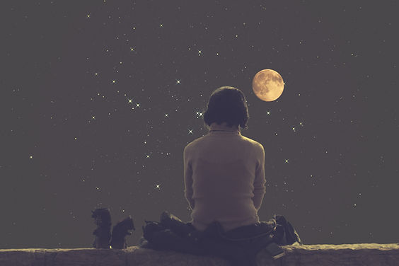 Woman looking at the Moon in a night sky.