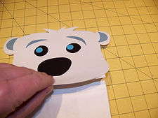 Kidfunideas.com Polar bear paper bag puppet picture of attaching the face to the bag