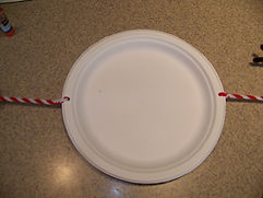 Kidfunideas.com paper plate snowman craft picture of ataching the arms to the body piece