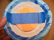 Kidfunideas.com Paper bowl flying saucer and alien craft - picture of securing the alien into the cockpit