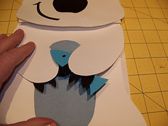 Kidfunideas.com polar bear paper bag puppet picture of attaching the fish to the hand
