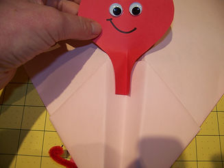 Kidfunideas.com valentine's paper airplane picture of attaching the heart buddy to the plane