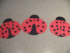 Kidfunideas.com my little ladybug craft. picture of attaching the dots to the ladybug