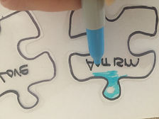 Kidfunideas.com Autism Awareness bracelet craft picture of applying the color to the puzzle pieces