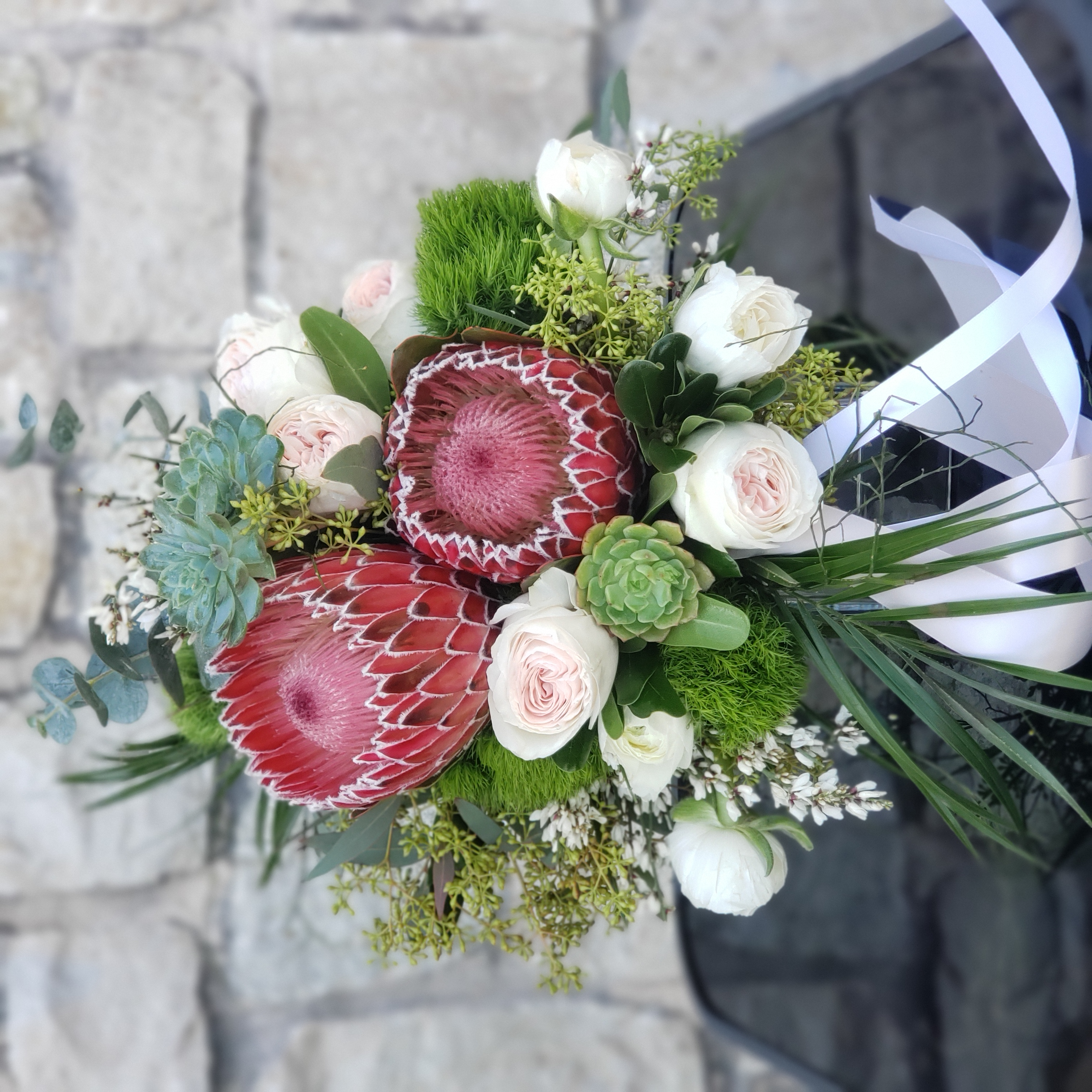bridal bouquet with protea and ranunculu