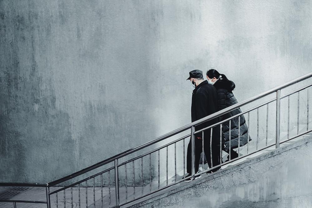 Casal desce escada de máscara