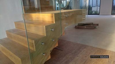 Guarda corpo de vidro em escada de madeira.