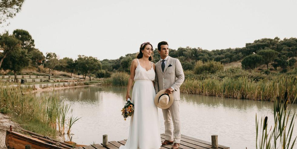 Bride and groom posing on bridge at lake