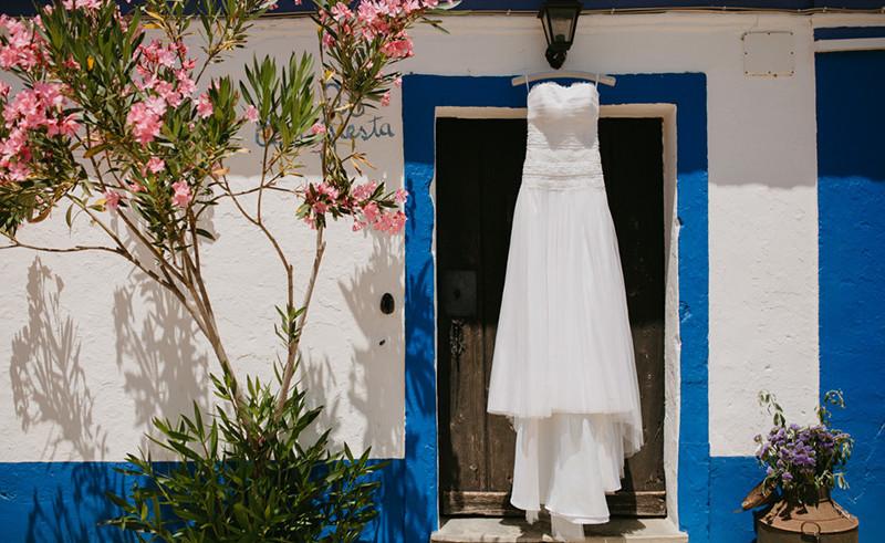Weddingdress in front of old door of Alentejano house in Portugal