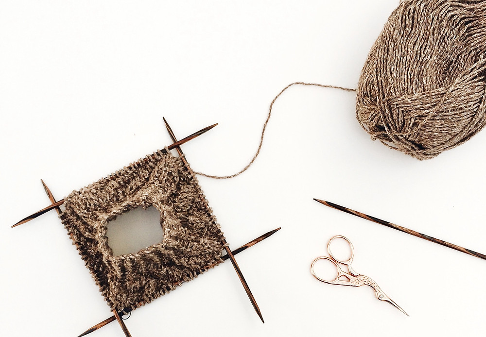 DIY items. Natural fabric used for crochet square stitching. With a golden scissor in bird-shape to the side