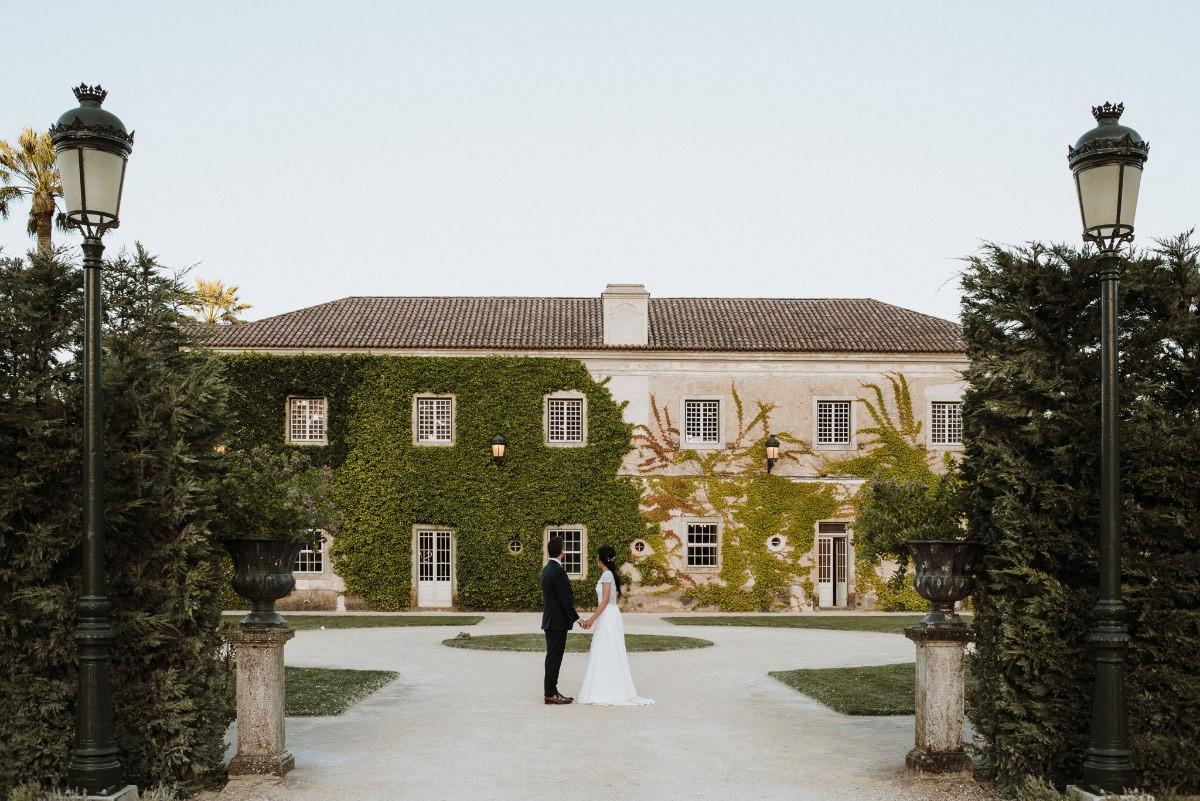 Bride & groom posing in front of historical wedding venue in Portugal