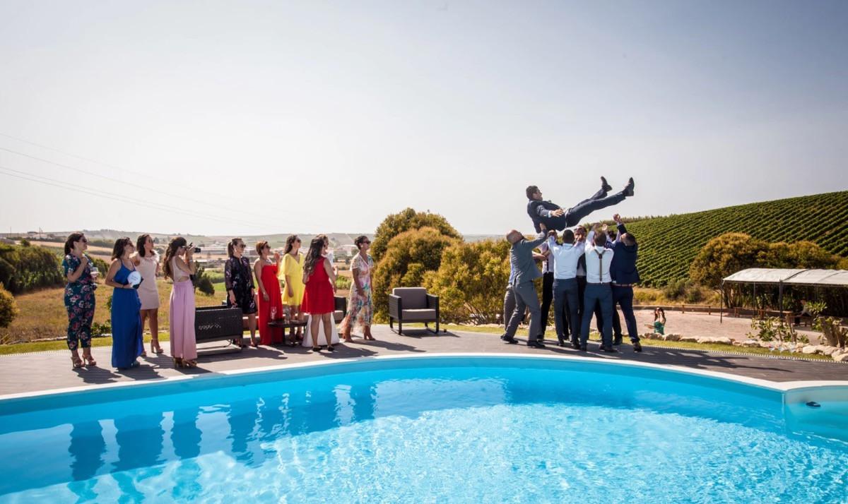 Groomsmen throwing groom in the air near swimmingpool
