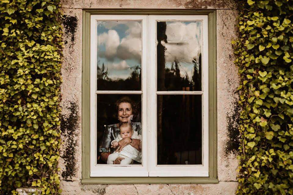 Grandmother and grandchild looking out of window to wedding ceremony