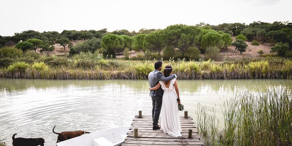 Bride & groom looking over the lake at wedding venue in Alentejo