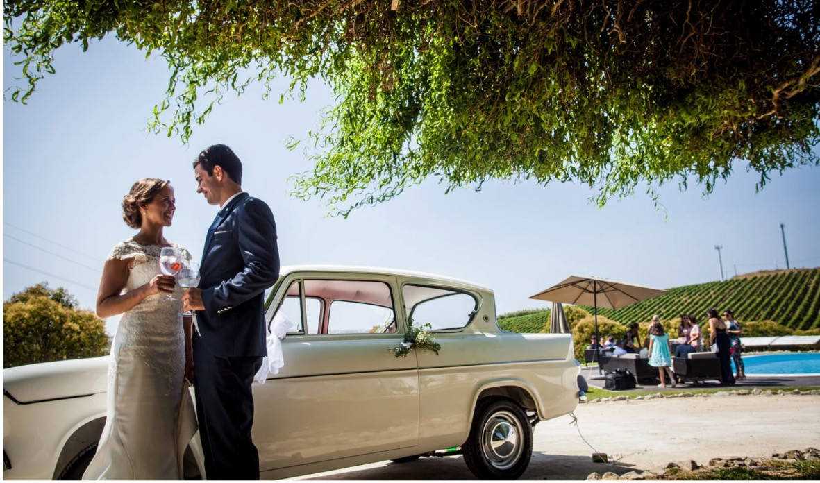 Bridalcouple with wedding car arriving to venue