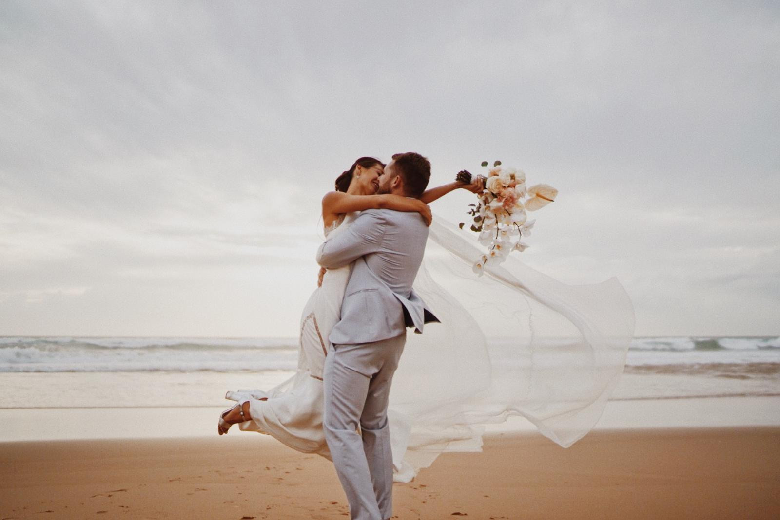 Groom lifts up bride on the beach