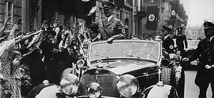 Adolf Hitler, the Chancellor of Germany, in a 1930s military parade, while in a Mercedes-Benz car.