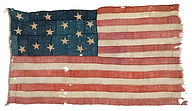 Fifteen star American flag, 1795-1818 pattern, from a merchant brig captured by HMS Borer, Captain Richard Coote during the War of 1812. It is made of hand-woven wool bunting with cotton stars and is hand-sewn.