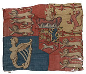 Royal Standard (1801-1816) : Object details: Object IDAAA0810 DescriptionA Royal Standard (1801-16), made of hand-sewn, wool bunting. The design is appliquéd with the details painted. It belonged to Lieutenant James Everard (1796-1825). The comparatively crude version of the royal arms has some losses at the fly end of the flag. The surface is distorted by repairs to tears and there is no hoist, the edge of the flag is simply turned over the rope. The standard is quartered with the arms of England (in the first and fourth quarters), Scotland and Ireland, with an inescutcheon containing the arms of Hanover overall, the crown of Charlemagne in the centre and an electoral bonnet on top. The electoral cap is only present on the Royal Standard between 1801 and 1816. When the union of the Irish and Westminster parliaments took place in 1801, with corresponding changes in flags and banners, George III took the opportunity to abandon the title of King of France. The royal arms were altered,