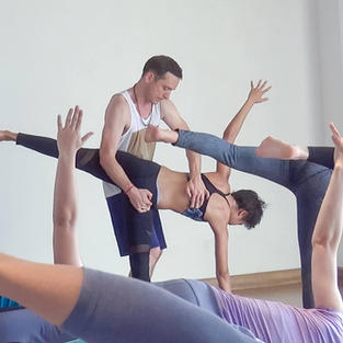 Adrian Cox adjusting ardha chandrasana yoga pose