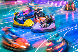 Young people driving bumper car at amuse