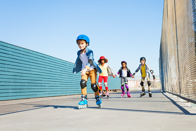 Boy playing roller skates with friends o
