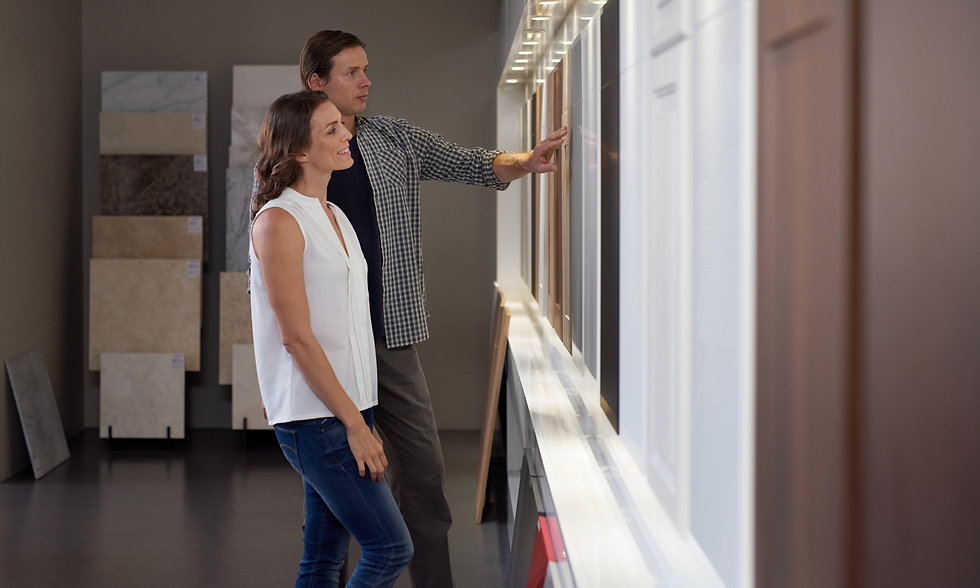 Couple looking at different materials and samples in modern kitchen shop showroom while de