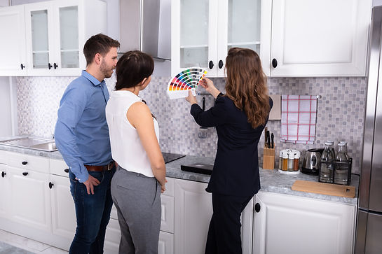 Young Female Real Estate Designer Showing Swatch Palette In New House To Couple.jpg