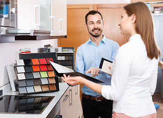 Competent positive seller consulting female customer in store of kitchen furnishing and ap