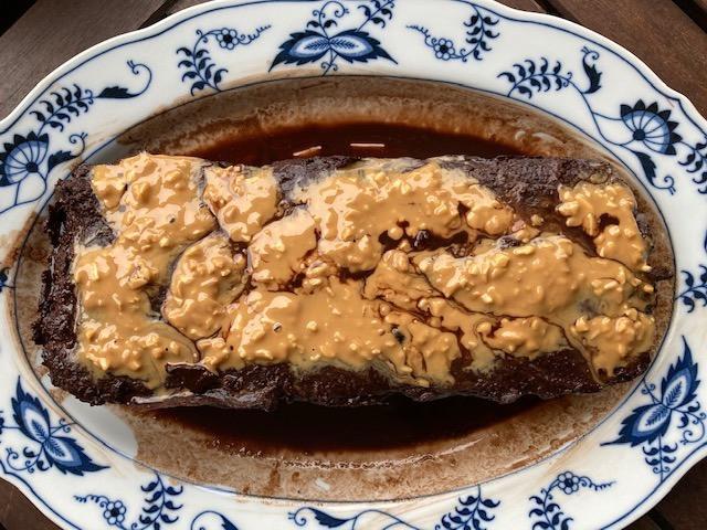 Schoko-Erdnuss-Kuchen auf blau weißem Teller