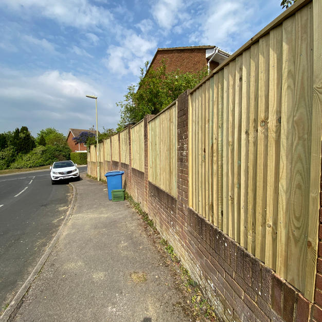 Featheredge fencing between brick walls in Yately.