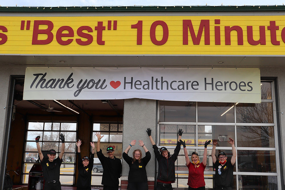 Super Lube employees under a Thank You Healthcare Heroes banner jumping for joy