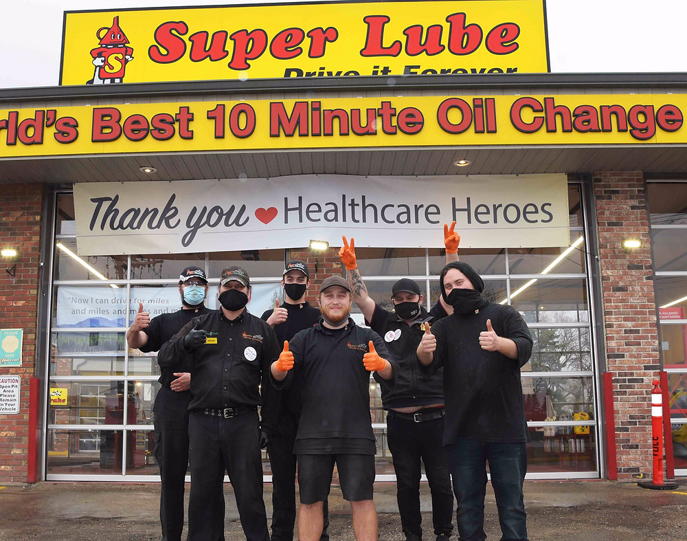 Super Lube employees in front of a Thank You Healthcare Heroes banner