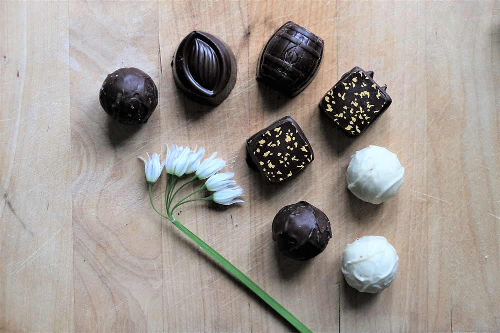 Eight truffles of different kinds and a single snowdrop flower on a wooden chopping board