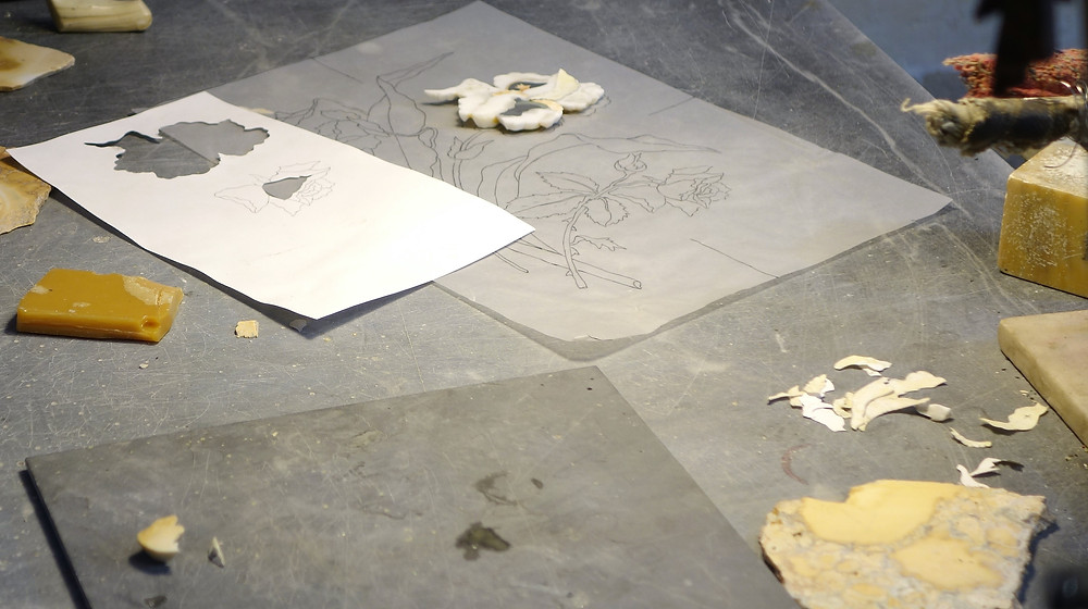 Design drawn in pencil is cut from hard stone