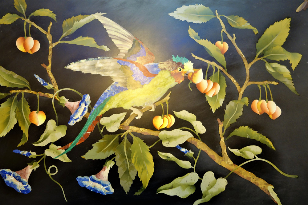 A Pietra Dura work depicting a colourful budgie sitting on a branch of a peach tree with spread wings eating peaches