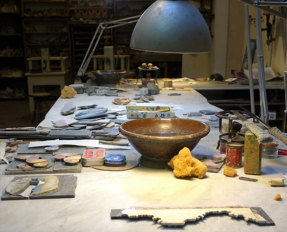 A Pietra Dura Workshop with a worktable littered with stone platelets, tools and a bowl of water