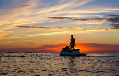 silhouette of a man on a jet ski in the