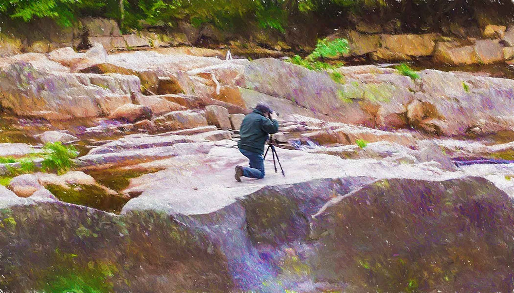 The photographer kneeling to take a photo from a boulder by the waterfall