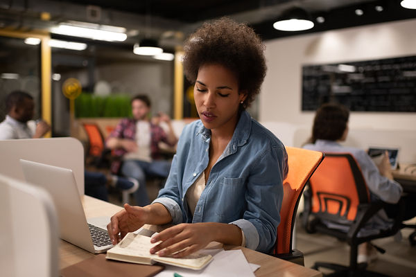 black-woman-reading-notes-in-office-U6SU