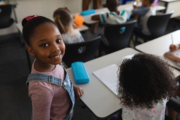 smiling-black-schoolgirl-standing-and-lo