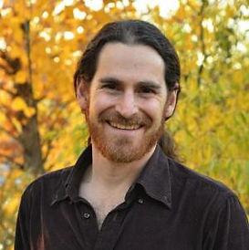 Headshot of a long-haired bearded man