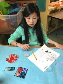 5th grader creating her glass tiles.