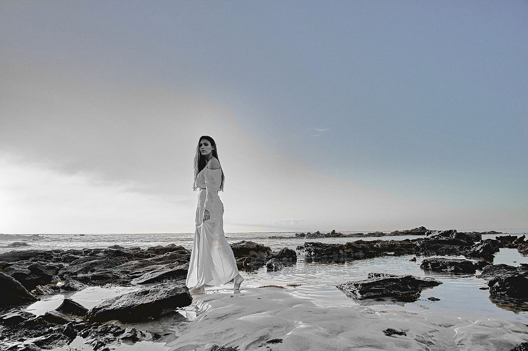 A lady standing near the sea depicting experiential partnership and luxury