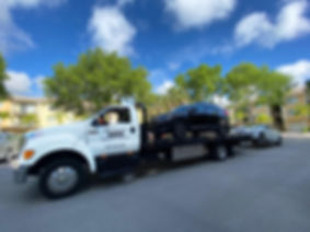 Bill Tyson's Delivery Truck with vehicles in tow