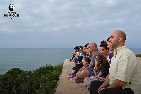 Pessoas meditando em miradouro vendo o mar
