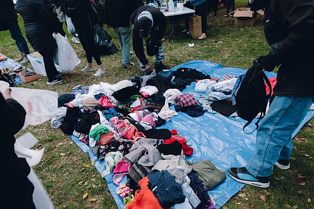 Photo of clothes folded on a tarp for weekly mutual aid